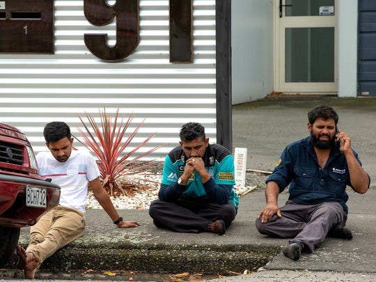 Grieving members of the public sit on a curb following a shooting resulting in multiple fatalies and injuries at the Masjid Al Noor on Deans Avenue in Christchurch, New Zealand, March 15, 2019.