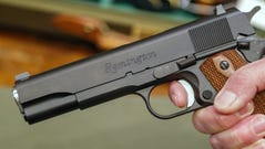 File picture: A salesperson holds a handgun at a firearms