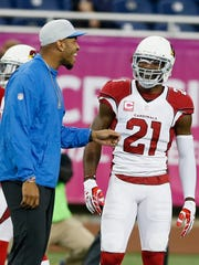 Injured Detroit Lions Eric Ebron talks with Arizona Cardinals  Patrick Peterson on the field as the teams warmed up for their football game on Sunday, October 11, 2015, in Detroit. Julian H. Gonzalez/Detroit Free Press