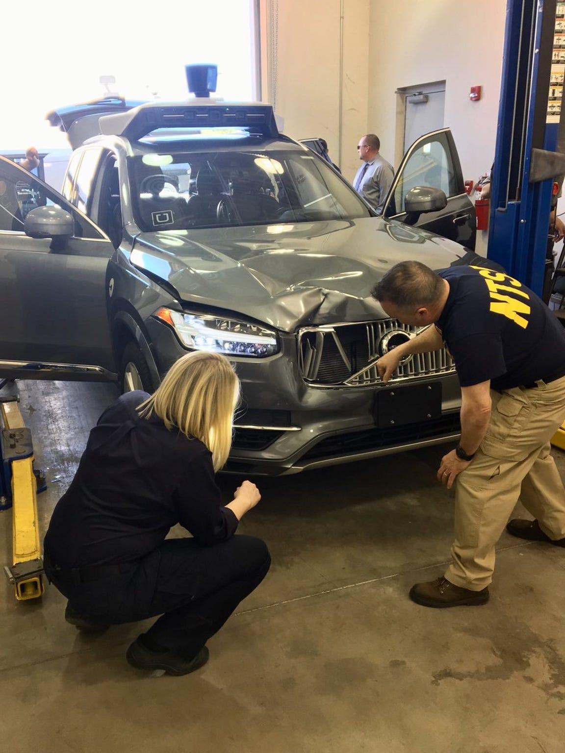 NTSB investigators examine a self-driving Uber vehicle