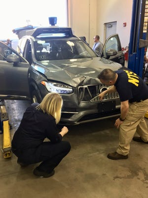 NTSB investigators examine a self-driving Uber vehicle hit and killed a woman in Tempe in March 2018.