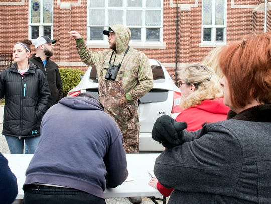 A man directs volunteers before a search for  Madison