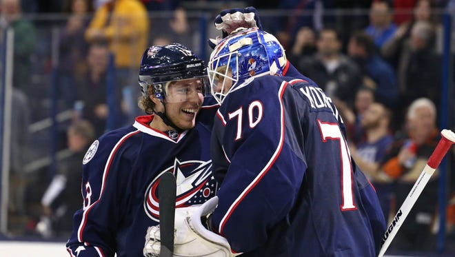 Columbus Blue Jackets right wing Cam Atkinson (13) celebrates with goalie Joonas Korpisalo (70) after defeating the Anaheim Ducks at Nationwide Arena.