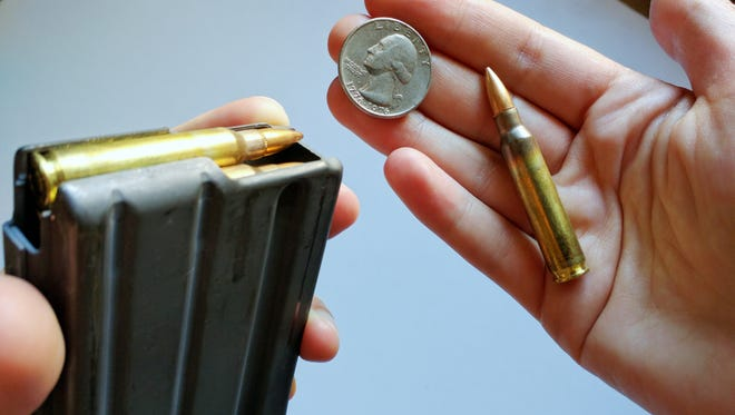 A 30-round magazine filled with .223-caliber ammo (with a quarter for size comparison).