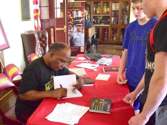 Amateur wrestling legend Carl Adams signs a copy of