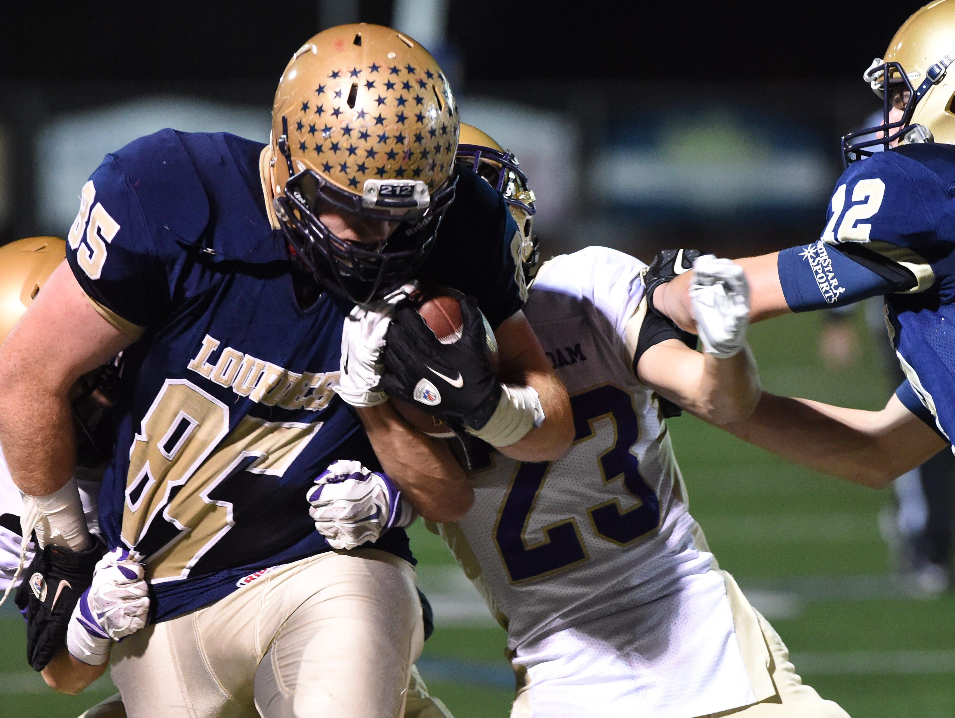 Lourdes' Chris Mulvey is taken down by Amsterdam's defense during the Class A semi final at Dietz Stadium.