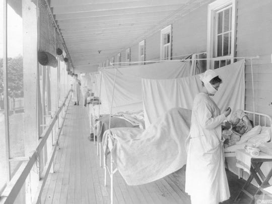 FILE - In this November 1918 photo made available by the Library of Congress, a nurse takes the pulse of a patient in the influenza ward of the Walter Reed hospital in Washington. Science has ticked off some major accomplishments over the last century. The world learned about viruses, cured various diseases, made effective vaccines, developed instant communications and created elaborate public-health networks. Yet in many ways, 2020 is looking like 1918, the year the great influenza pandemic raged. (Harris & Ewing/Library of Congress via AP, File)