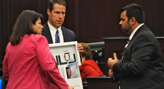 State Attorney Angela Corey, left, talks with Michael Dunn's defense lawyer, Cory Strolla, right, about the display of items found in the pockets of the victim Jordan Davis, held by Assistant State Attorney John Guy, center, on Day 3 of Dunn's trial Feb. 8 in Jacksonville, Fla.