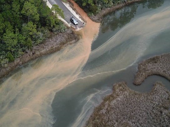 Images shot by a drone show how red clay sediment seeps