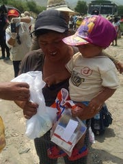 A woman and child receive supplies from Rotary in Trujillo, Peru.