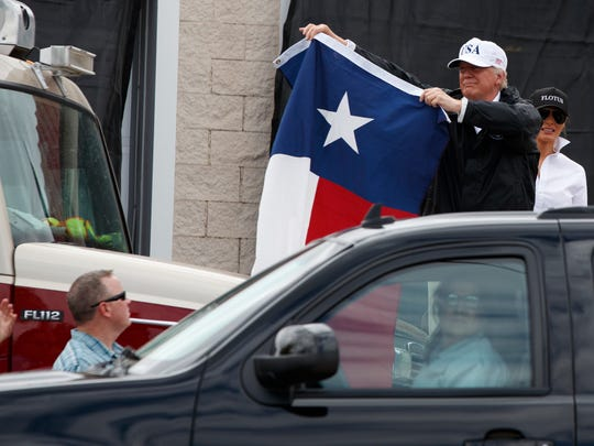 President Trump holds up a Texas flag after speaking