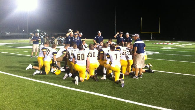 The 2014 Ithaca football huddles before their opener against Clare.
