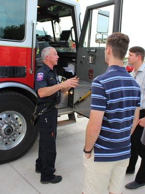 Firefighter Randell Clark, left, talks about what the ladder truck from Station No. 1 carries and can do during Monday's Abilene Academy tour of Station No. 3, one of the city's three new facilities.