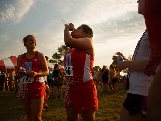 Wendy Flores, center, gets a drink after running a