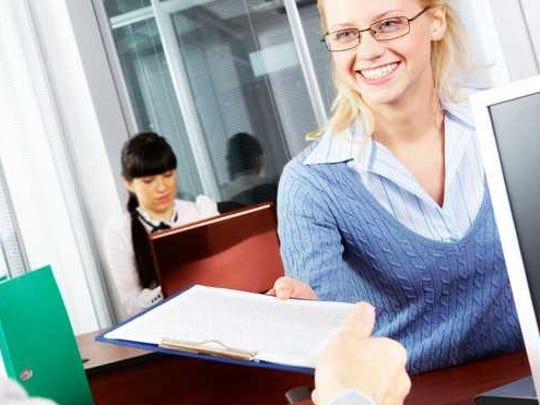 A bank teller hands a customer some paperwork.
