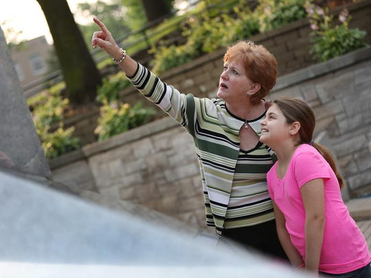 Donna Cadwallader, left, shows her granddaughter, Libby Cadwallader, 8, Libby's great-grandfather's name, John Cadwallader, on the USS Indianapolis Memorial on the Canal Walk downtown, Tuesday, June 9, 2015. The Lost at Sea program is honoring sailors who died aboard the USS Indianapolis. Cadwallader is one of the 900 sailors who died when the ship sank after being torpedoed.