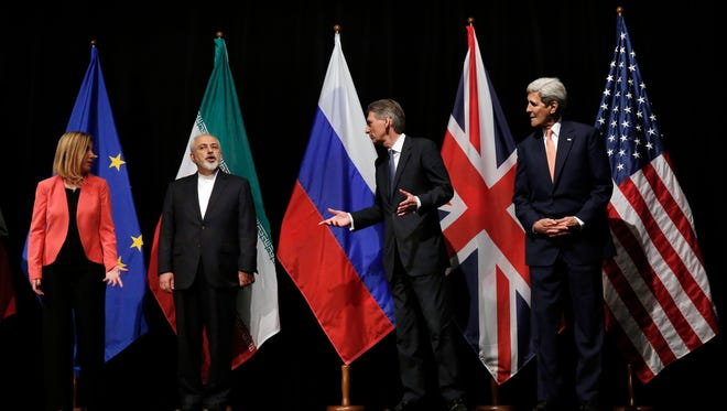 U.S. Secretary of State John Kerry, right, British Foreign Secretary Philip Hammond, 2nd from right, and European Union High Representative for Foreign Affairs Federica Mogherini, left, talk to Iranian Foreign Minister Mohammad Javad Zarif in Vienna, July 14, 2015. After 18 days of negotiation, world powers and Iran struck a landmark deal Tuesday to curb Iran's nuclear program in exchange for billions of dollars in relief from international sanctions.