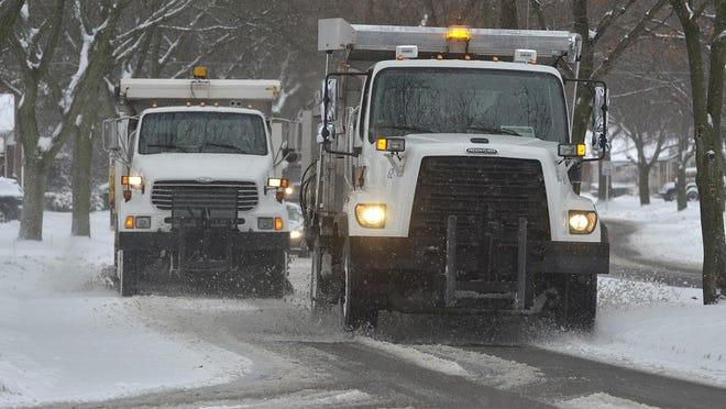 City of Livonia trucks plow Lyndon east of Farmington on Thursday morning.