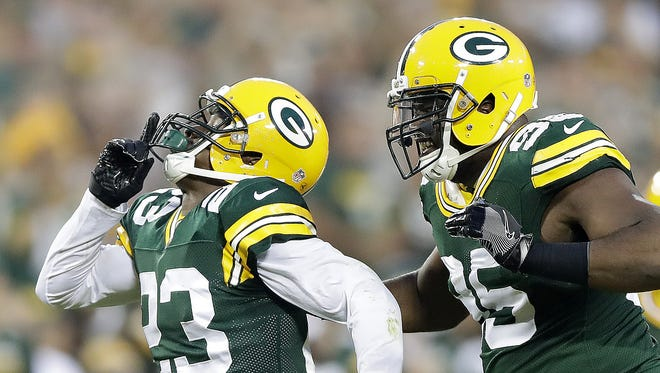 Green Bay Packers cornerback Damarious Randall (23) celebrates his interception with defensive end Datone Jones (95) during the game against the Oakland Raiders at Lambeau Field.