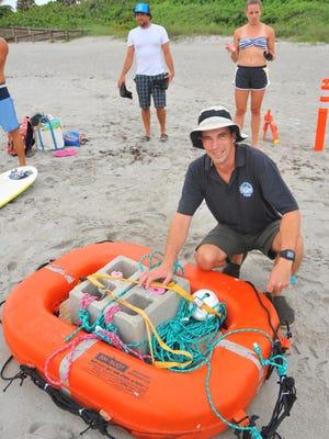 Robert Weaver, assistant professor of ocean engineering at Florida Institute of Technology, checks the deployment raft.