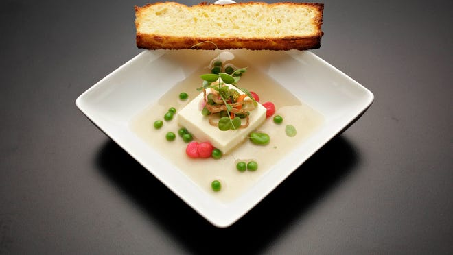 Ode to spring: A chilled pea consommé came studded with peas, fava beans and pearls of poached radish. It was served with shallot-infused custard and toasted duck-fat brioche.
