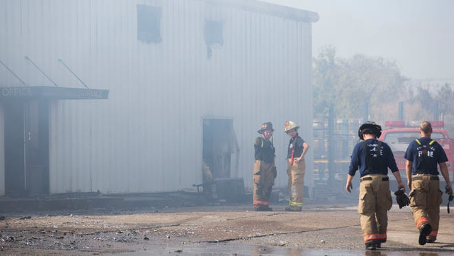 Evansville firefighters discuss how to proceed after the fire is under control and mostly put out at Piranha Mobile Shredding and Recycling in Evansville on Friday morning.