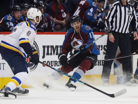 Colorado Avalanche right wing Rene Bourque, right, flips the puck in the air as St. Louis Blues defenseman Joel Edmundson covers in the first period of an NHL hockey game Tuesday, March 21, 2017, in Denver. (AP Photo/David Zalubowski)