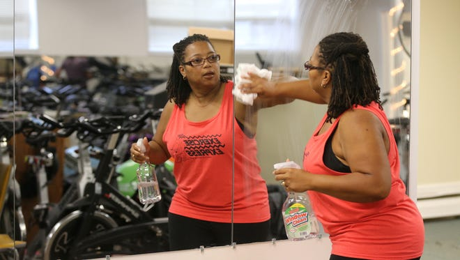 Shaun Reed cleans mirrors and exercise equipment at Exercise Express .