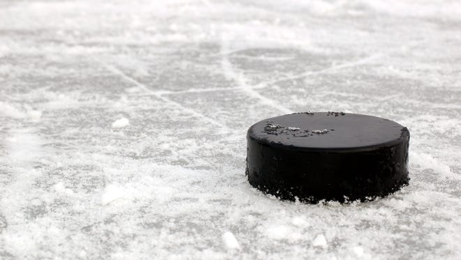 Hockey puck on ice rink file photo.