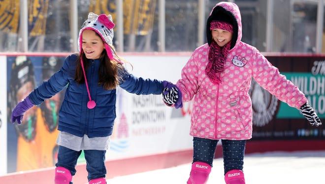 Ava Fuentes, left, and Caroline Carney, skate together on the ice rink at Bridgestone Winter Park Sunday January 10, 2016.