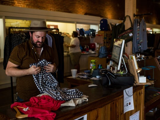 Ross Fontenot, store owner at Genterie Supply Co., folds clothing as customers shop during Small Business Saturday in Lafayette, La., Saturday, Nov. 28, 2015. Small Business Saturday, which serves as an alternative to the Black Friday shopping event, is intended to encourage shoppers to purchase goods and services from locally-owned small businesses.