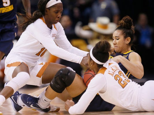 Texas guard Lashann Higgs, left, West Virginia guard Alexis Brewer, right, and Texas guard Ariel Atkins (23) fight for the ball in the first half of an NCAA college basketball game at the Big 12 Conference tournament in Oklahoma City, Sunday, March 5, 2017. (AP Photo/Sue Ogrocki)