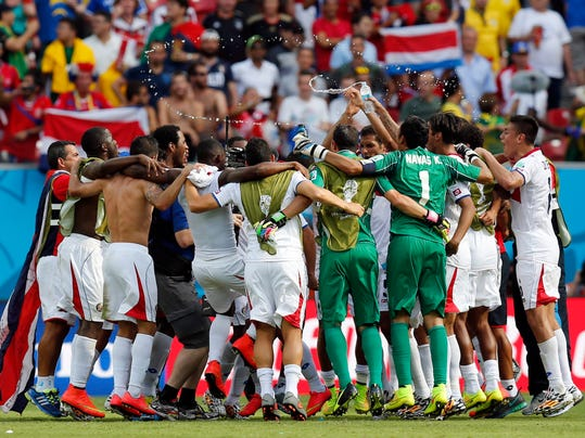 Costa Rican players celebrate after the group D World Cup soccer match between Italy and Costa Rica at the Arena Pernambuco in Recife, Brazil, Friday, June 20, 2014. Costa Rica won the match 1-0. (AP Photo/Frank Augstein)