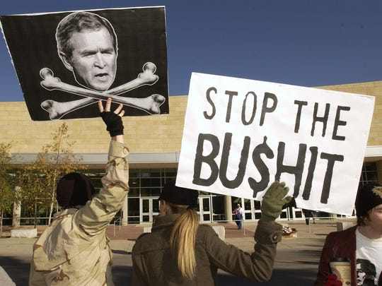 Individuals protest outside President George W. Bush's