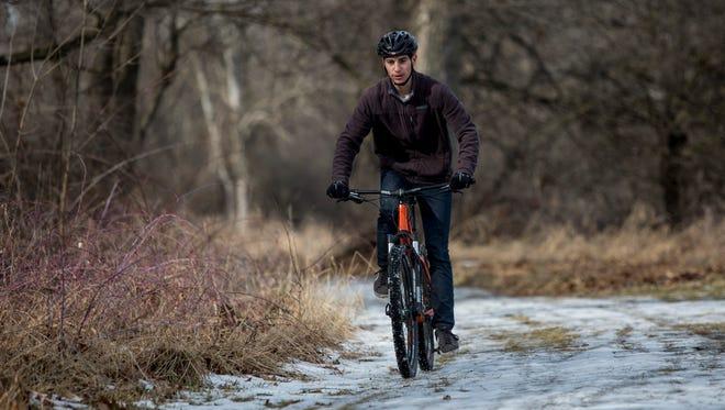 Blake Iskra, 18, of Columbus Township, rides his mountain bike along a trail Jan. 30, 2016 at Columbus County Park in Columbus Township.