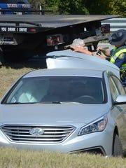Michigan State Police Trooper Tim Lane checks injuries
