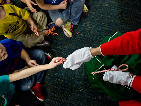 Students are given candy canes during a party Wednesday, Dec. 16, 2015 at Millside Elementary School in Algonac.