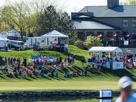 Spectators gather along the 18th hole to watch the