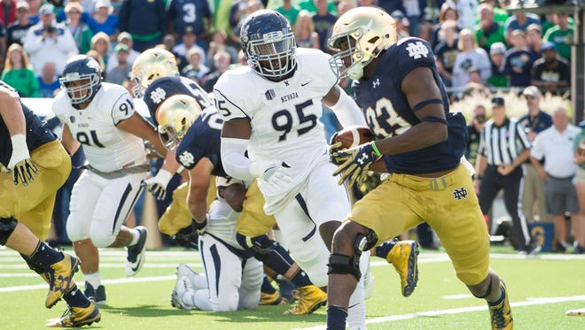 Wolf Pack defensive end Patrick Choudja tries to chase down Notre Dame running back Josh Adams during a game earlier this season.