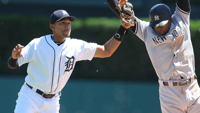 Tigers second baseman Dixon Machado prepares to throw to first after tagging out Didi Gregorius, right, during the fifth inning Monday in Game 1 at Comerica Park.