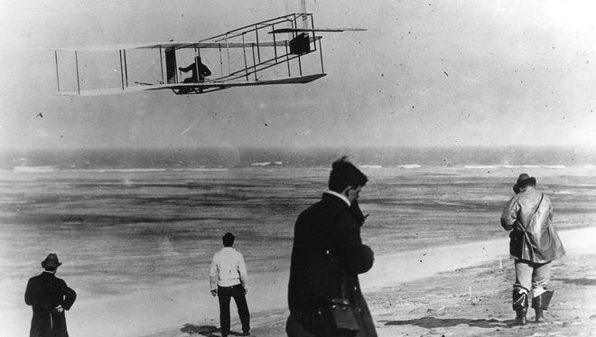 In this undated file photo, Orville and Wilbur Wright test their airplane on a beach.