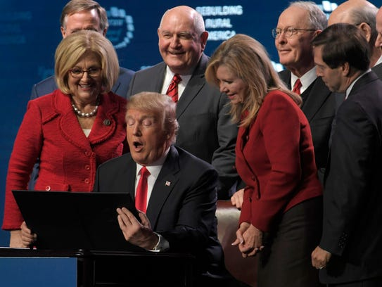 Rep. Diane Black, left, flanks President Donald Trump as he signs an executive order Jan. 8 in Nashville.