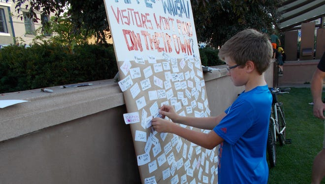 Residents write their favorite ideas on stickers and put them on the board at Concert on the Square on Wednesday night.