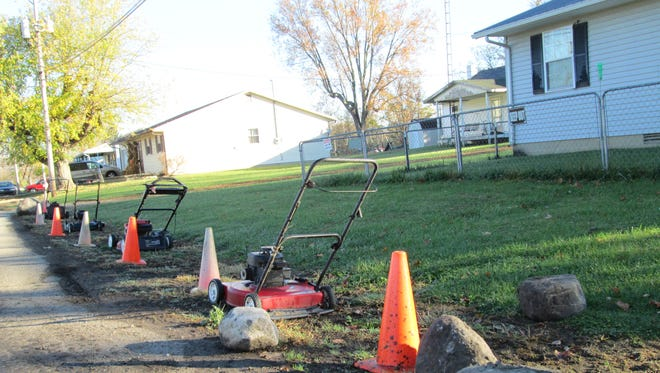 Ronald Wolf ringed his lawn on Harrison Street in Liberty with lawn mowers, cones and a boulder to force drivers to stay on the pavement.