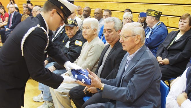 C/CMC Peter Toscak presents our National Ensign to the eldest veteran in attendance, John Kuhtik, a World War II veteran, at the Linden High School NJROTC Veterans Day ceremony.