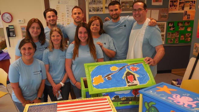 Associates of Parsippany-based Cornerstone Search Group with the three toy boxes they built for local veterans' children at Cornerstone Family Programs in Morristown. After a tour of the facilities, the group spent the afternoon assembling, painting and stenciling the toy boxes.