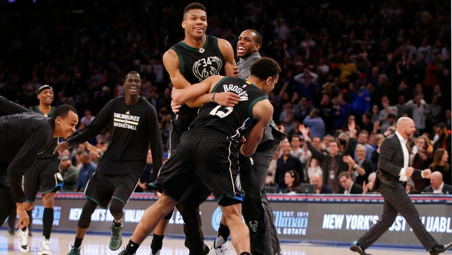 Teammates including Malcolm Brogdon celebrate with Bucks forward Giannis Antetokounmpo after he made a two point buzzer-beater to defeat the New York Knicks.