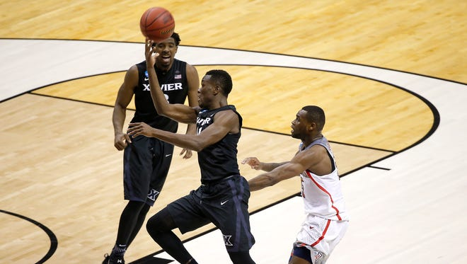 Xavier Musketeers guard Malcolm Bernard (11) throws the ball up in the air as time expires in the second half.