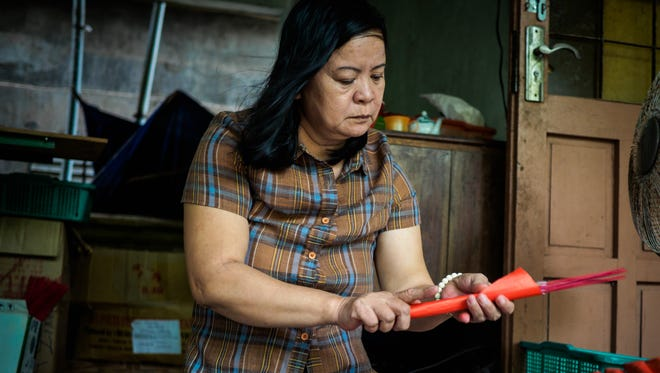 Nguyen Thi Cuc, 58, who lost both her legs to an unexploded cluster bomb dropped during the Vietnam War, wraps incense sticks to make a living in Quang Tri Province, Vietnam.