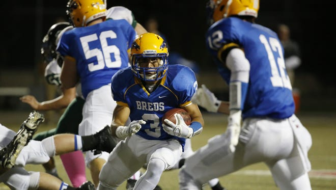Newport Central Catholic's Jacob Smith breaks through the line for a touchdown run  during their football game against Bishop Brossart.